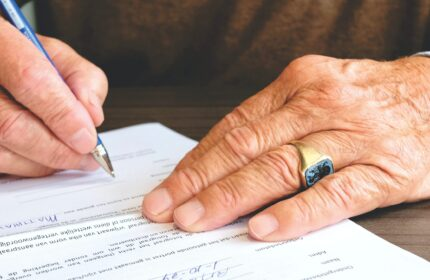 man signing document with pen