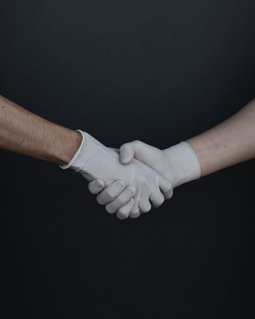 people shaking hands in latex gloves